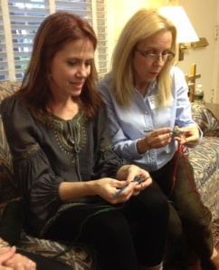 Brenda shows Jayne some crochet stitches.