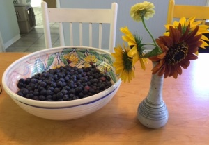 Kitchen brightened by fresh fruit and fresh flowers.