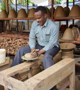 Surrounded by drying water filters, Mesiaki demonstrates his foot powered pottery wheel.
